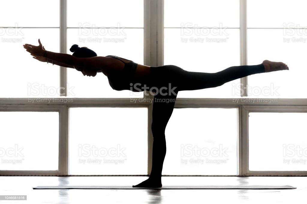 Young sporty attractive woman practicing yoga, doing Warrior Three Young sporty attractive woman practicing yoga, doing Warrior III, exercise, Virabhadrasana 3 pose, working out, wearing sportswear, indoor full length, at yoga studio, side view silhouette Active Lifestyle Stock Photo
