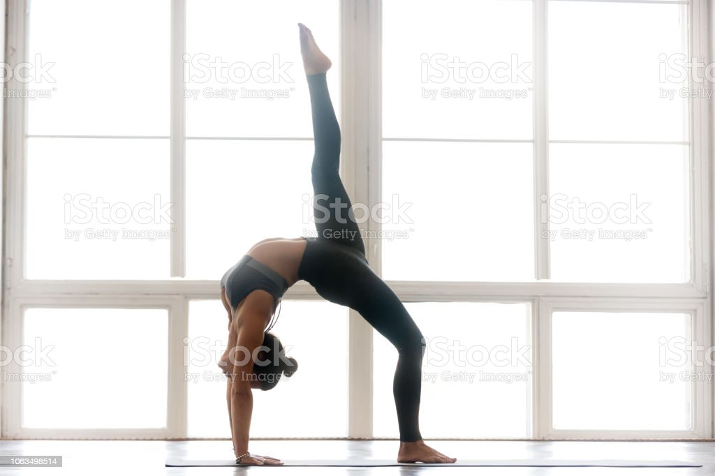 a3a578fca8cab Young sporty attractive woman practicing yoga, One legged Wheel pose - Stock  image .