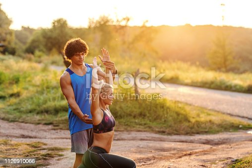 511849865istockphoto Young sporty Caucasian man with curly hair helping his girlfriend to do fitness exercise. Nature exterior, sunny summer day. 1126910066
