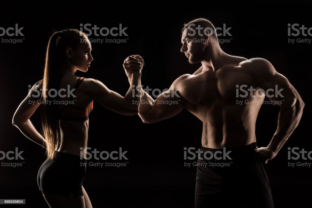 young sporty couple holding hands isolated on black stock photo