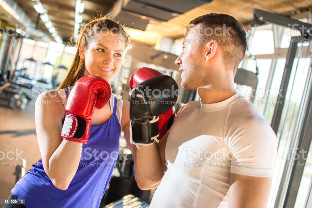 Young sporty couple in sportswear with boxing gloves practicing boxing at the gym. stock photo