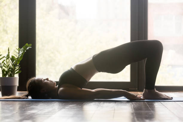 Young sporty doing pilates or yoga Glute Bridge pose Young sporty woman practicing yoga, doing dvi pada pithasana exercise, Glute Bridge pose, working out, wearing sportswear, grey pants and top, indoor full length, yoga studio shoulder stand stock pictures, royalty-free photos & images