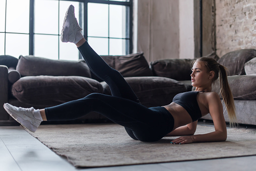 istock Young sporty female doing abs workout in living room performing alternate leg raising and crunch exercise 821731496