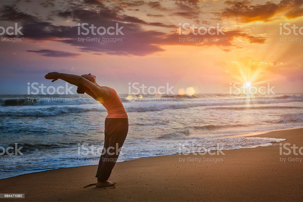 Young sporty fit man doing yoga Sun salutation Surya Namaskar stock photo