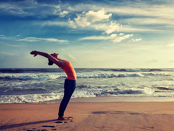 Young sporty fit woman doing yoga Sun salutation Surya Namaskar Vintage retro effect hipster style image of young sporty fit woman doing yoga Sun salutation Surya Namaskar pose Hasta Uttanasana on tropical beach on sunset sun salutation stock pictures, royalty-free photos & images
