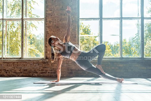 Young sporty fit woman trainer do practice individual hatha yoga instructor training Vasisthasana side plank arm leg support balancing pose modern gym mat wooden floor window healthy lifestyle concept