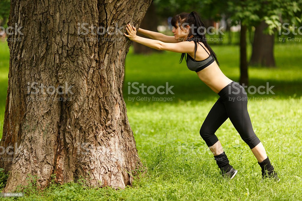 Young sporty full length girl doing stretching leaning on tree royalty-free stock photo