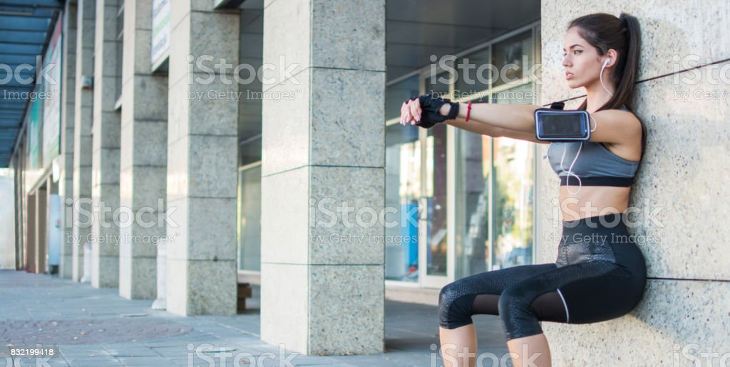 Young sporty girl doing wall sitting exercise urban outdoors. stock photo