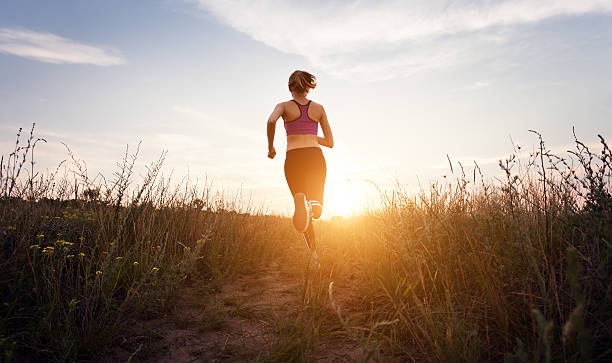 Young sporty girl running on a rural road at sunset stock photo