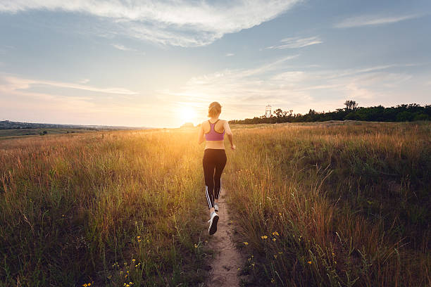 Joven deportivo de chica corriendo en la carretera rural en puesta de sol - foto de stock