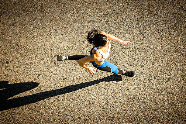 young sporty looking woman running - marathon stock photos and pictures