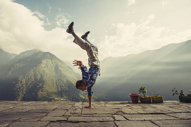 Young sporty man doing handstand exercise in beautiful mountain landscape stock photo