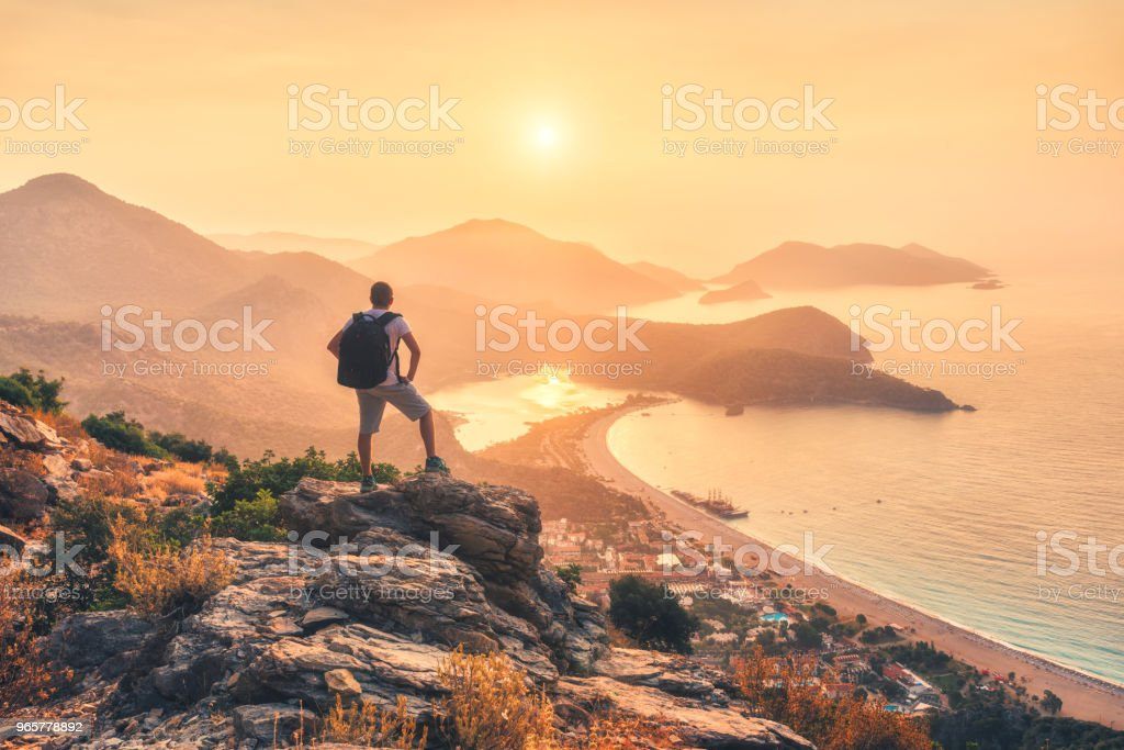 Young sporty man with backpack standing on the top of rock and looking at the seashore and mountains at sunset in summer. Scene with man, sea, mountain ridges and orange sky with sun. Oludeniz, Turkey - Royalty-free Adult Stock Photo