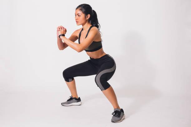 deportiva muscular joven haciendo sentadillas aisladas sobre fondo blanco. mujer en ropa de deporte, realizar ejercicio - agacharse fotografías e imágenes de stock