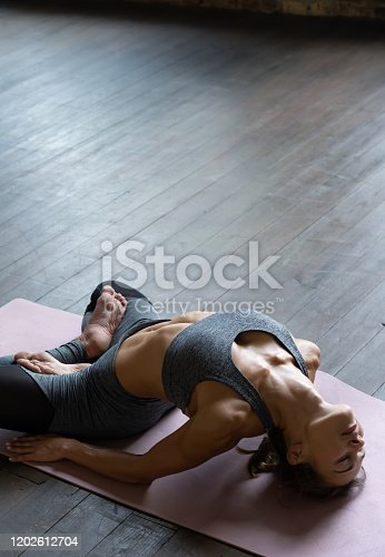 Young sporty slim fit woman trainer doing exercise practice hatha yoga instructor training matsyasana pose backbend fish position lotus legs on mat wooden floor in yoga studio, vertical view