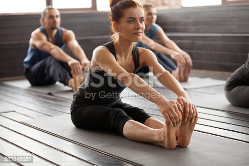 istock Young sporty woman and a group people in paschimottanasana pose 922345052