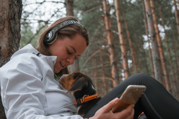 Young sporty woman and her best friend relaxing in nature stock photo