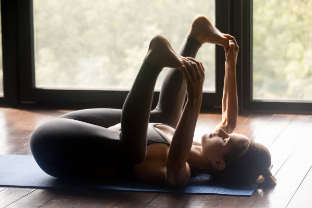Young sporty woman doing Happy Baby exercise Young sporty woman practicing yoga, doing Happy Baby exercise, Ananda Balasana pose, working out, wearing sportswear, grey pants and top, indoor full length, yoga studio apanasana stock pictures, royalty-free photos & images