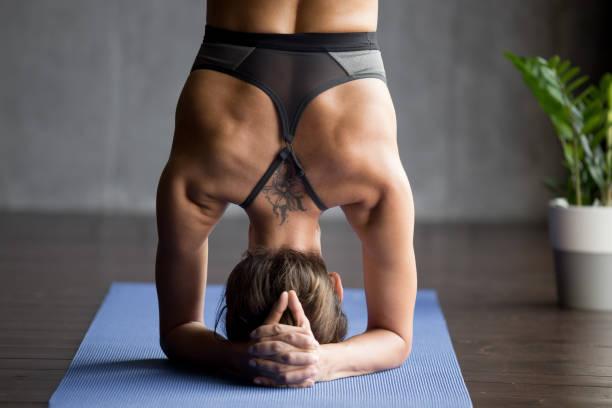 junge sportliche frau kopfstand übung, nahaufnahme - gymnastik tattoo stock-fotos und bilder