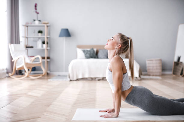 Young sporty woman doing morning exercise in living room on mat. stock photo