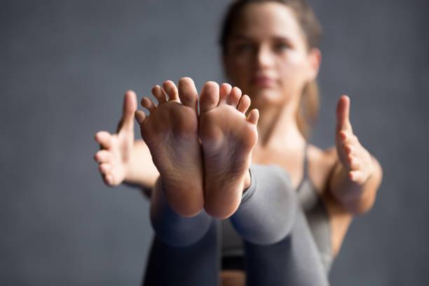 close-up van jonge sportieve vrouw doen paripurna navasana oefening - pilates stockfoto's en -beelden