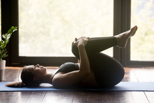 Young sporty woman doing pilates or yoga Apanasana pose Young sporty woman practicing yoga, doing Knees to Chest exercise, Apanasana pose, working out, wearing sportswear, grey pants and top, indoor full length, yoga studio bending stock pictures, royalty-free photos & images