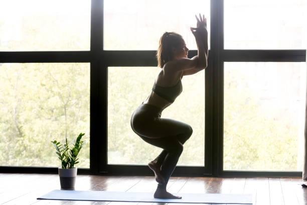 junge sportliche frau yoga eagle sport - schlanke waden stock-fotos und bilder