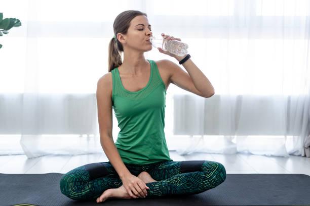 jonge sportieve vrouw drinkwater uit plastic fles - woman water stockfoto's en -beelden
