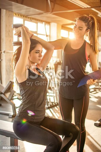 istock Young sporty woman having exercise class with assistance of personal fitness instructor in the gym. 890883234