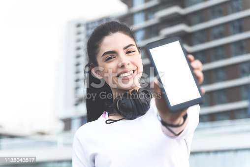 Portrait of attractive sporty brunette with beautiful smile showing smartphone with blank white screen with space for text, New generation technology and apps for tracking sports activity