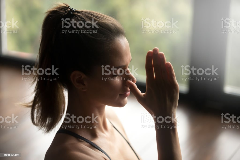 Young sporty woman in Alternate Nostril Breathing stock photo