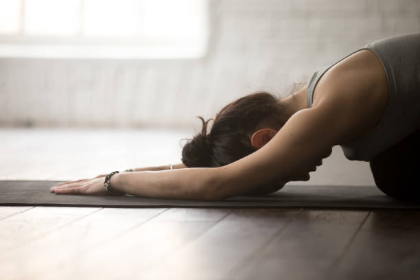 Young sporty woman in Balasana pose, white loft studio, closeup Young attractive sporty yogi woman practicing yoga concept, sitting in Child exercise, Balasana pose, working out, wearing sportswear, close up, white loft studio background, side view shoulder stand stock pictures, royalty-free photos & images