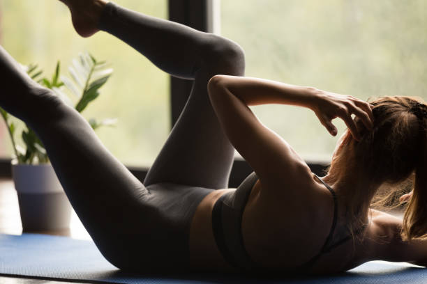 young sporty woman in bicycle crunches pose, close up - practicing stock pictures, royalty-free photos & images