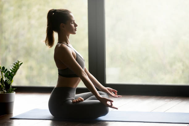 young sporty woman in half lotus pose, side view - yoga stock photos and pictures