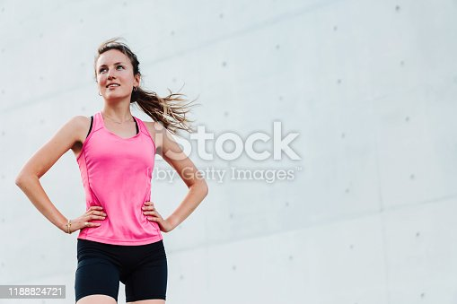 young sporty woman running in modern business district
