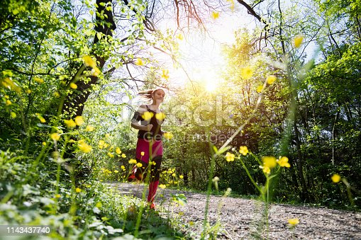 Young sporty woman jogging through the forest.