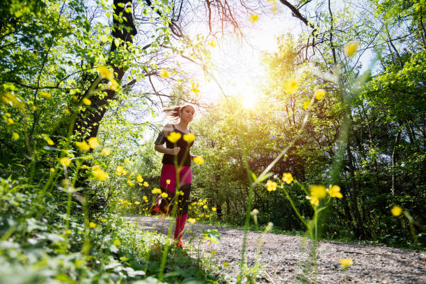 young sporty woman jogging through the forest. - corsa su pista femminile foto e immagini stock