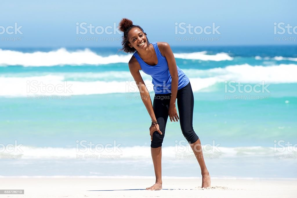 Young sporty woman laughing at the beach stock photo