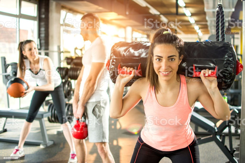 Young sporty woman lifting gym bag on shoulders with her friends in the background. stock photo