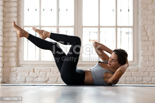 Young sporty woman practicing, doing crisscross exercise, bicycle crunches pose, working out, wearing sportswear, black pants and top, indoor full length, white sport studio