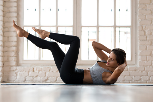 istock Young sporty woman practicing, doing bicycle crunches pose 1066259678