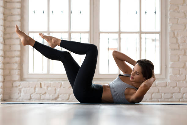 Young sporty woman practicing, doing bicycle crunches pose Young sporty woman practicing, doing crisscross exercise, bicycle crunches pose, working out, wearing sportswear, black pants and top, indoor full length, white sport studio abdominal muscle stock pictures, royalty-free photos & images