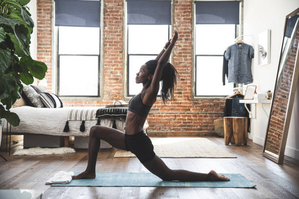Young sporty woman practicing yoga at home stock photo