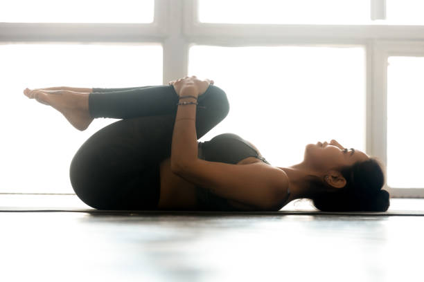 Young sporty woman practicing yoga, doing Knees to Chest exercise Young sporty attractive woman practicing yoga, doing Knees to Chest exercise, Apanasana pose, working out, wearing sportswear, grey pants, top, indoor full length, at yoga studio apanasana stock pictures, royalty-free photos & images