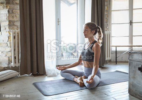 istock Young sporty woman practicing yoga 1184853146