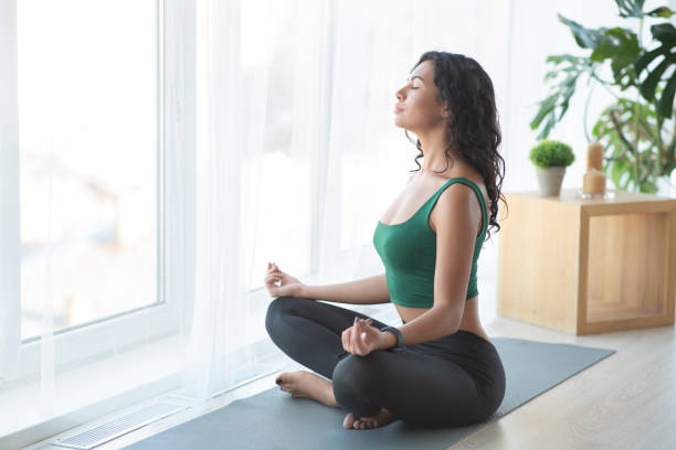 Young sporty woman practising yoga in lotus position Clear your thoughts. Young sporty woman practising yoga in lotus position, home atmosphere, copy space meditating stock pictures, royalty-free photos & images