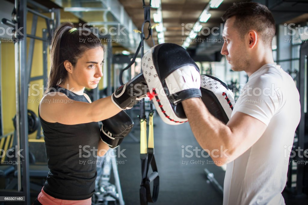 Young sporty woman punching her male partner with red boxing gloves at gym. photo libre de droits