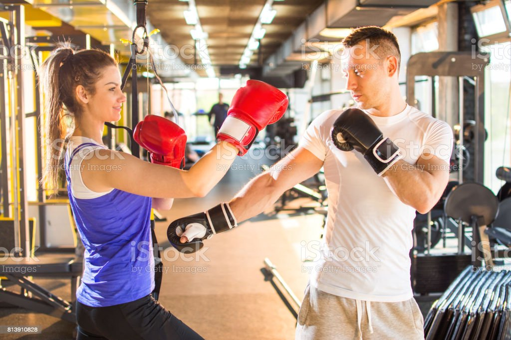 Young sporty woman punching her male partner with red boxing gloves at gym. stock photo
