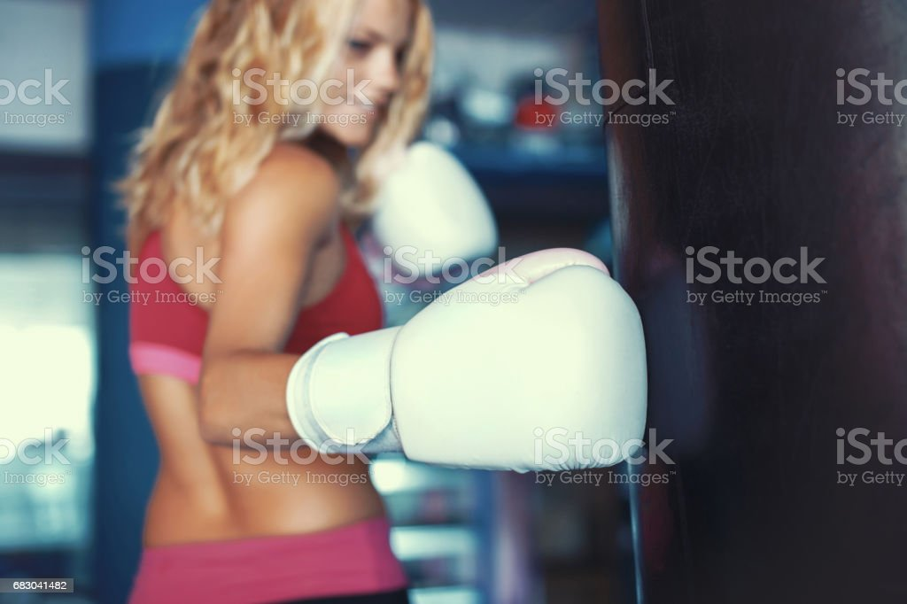 Young sporty woman punching into heavy bag in gym stock photo