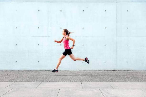 young sporty woman running  in front of concrete wall stock photo